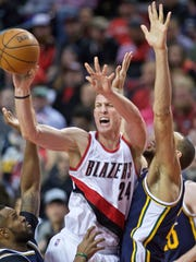 Portland Trail Blazers center Mason Plumlee, center, passes away from Utah Jazz center Rudy Gobert, right, and forward Trevor Booker, left, during the second half of an NBA basketball game in Portland, Ore., Wednesday, Jan. 13, 2016.