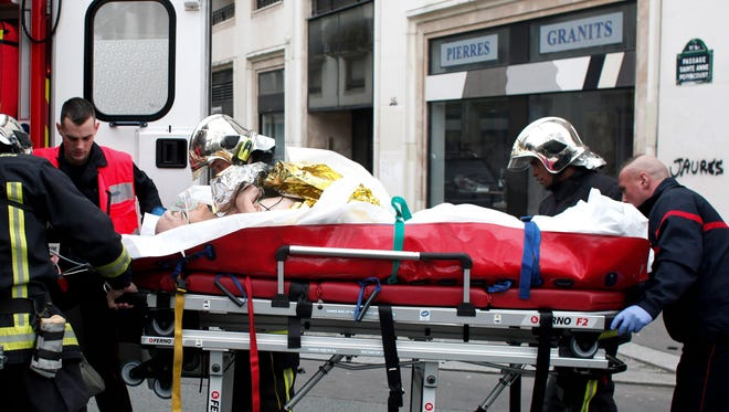 An injured person is transported to an ambulance after a shooting, at the French satirical newspaper Charlie Hebdo's office, in Paris on Jan. 7, 2015.