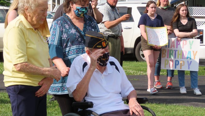 With his wife and daughter behind him, World War II veteran Art Smith salutes members of American Legion Devore-Quinn Post 486 as they parade past his home on the occasion of his 94th birthday.