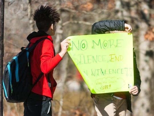 Students display signs protesting gun violence outside