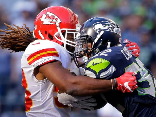 Seahawks running back Chris Carson is tackled by Chiefs