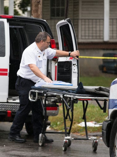 A medical examiner arrives on scene where two victims have died after a shooting at a house party on Woodward St. on Saturday, September 12, 2015. Six people were shot in total.