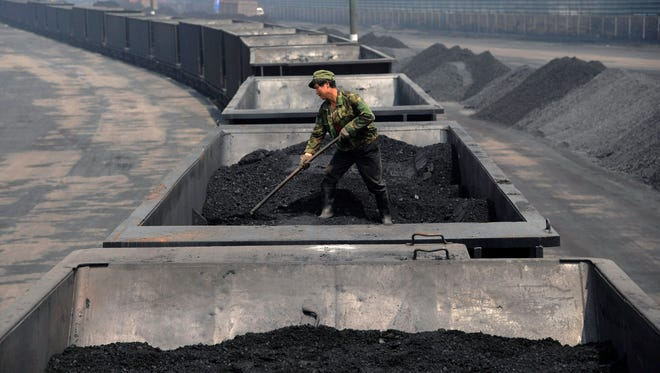 FILE - In this Wednesday, July 31, 2013, file photo, a worker levels the coal on a freight train in Taiyuan in northern China's Shanxi province. Spurred chiefly by China, the United States and India, the world spewed far more carbon pollution into the air last year than ever before, scientists announced Sunday, Sept. 21, 2014, as world leaders gather to discuss how to reduce heat-trapping gases.  (AP Photo/File) CHINA OUT