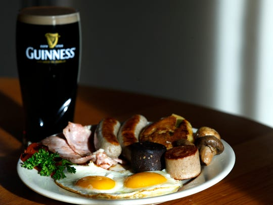 A traditional Irish Christmas breakfast with eggs, meats and tomatoes, with a Guinness on the side, from the Irish Rover.  Nov. 25, 2015