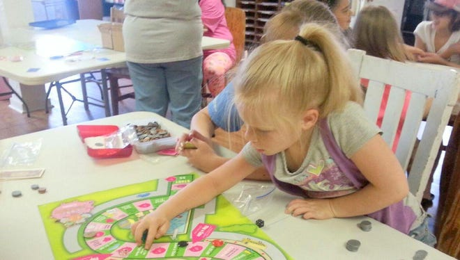 Kimberly Tavizon is seen playing the game in the program The Power of the Penny for the Girl Scouts of the Desert Southwest.