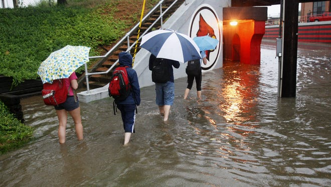U of L students waded through water at the viaduct at Third St. and Eastern Parkway in 2009.