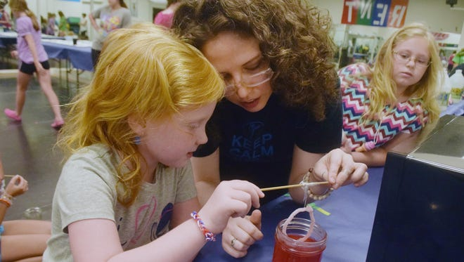 Katie Shuflin-Febuary (right) shows Olivia Zell, 5, the crystals that formed on a piper cleaner placed in a solution of Borax Laundry Booster, food coloring and hot water. As the water cools, the Borax creates crystals on the pipe cleaners. Just Dance is hosting a science camp to introduce young girls to the world of science, math, technology and engineering. The campers shaped piper cleaners and placed them in a solution of Borax, food coloring and hot water.