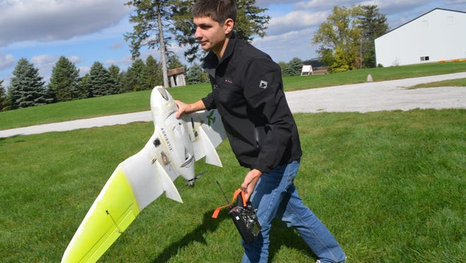 Kyle Miller, 21, carries his a drone before an Oct. 6 flight on his family's farm between Iowa City and Kalona.