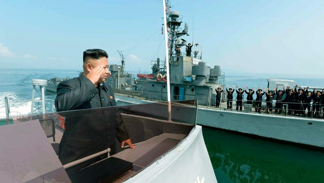 An undated file picture released by the Rodong Sinmun, the newspaper of the ruling North Korean Workers Party, shows North Korean leader Kim Jong Un saluting to military servicemen on a Navy ship, somewhere in North Korean waters.