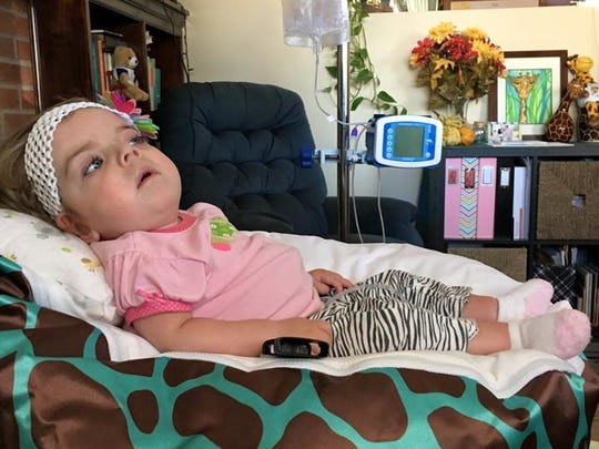 Tori Brackbill, 15 months old, sits at a chair in her