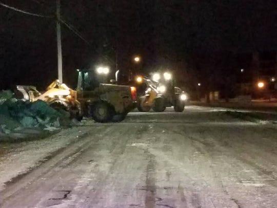Port Clinton street department crews work to remove ice coming off Lake Erie from West Lakeshore Drive on Friday night.