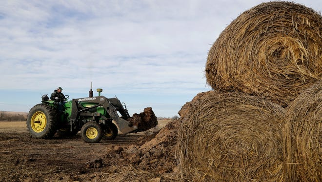 Matt Ubell scoops up a load of cattle feed on his farm near Wheaton, Kan., on Wednesday, Dec. 21, 2016. Ubell is one of many farmers taking out government farm loans to make ends meet in a turbulent farm economy.
