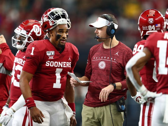 Dec 7, 2019; Arlington, TX, USA; Oklahoma Sooner head coach Lincoln Riley talks with quarterback Jalen Hurts (1) during a timeout from the game against the Baylor Bears in the 2019 Big 12 Championship Game at AT&T Stadium. Mandatory Credit: Matthew Emmons-USA TODAY Sports
