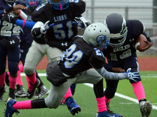 Luke Rayborn (No. 20) of the Canton Lions freshman team delivers a tackle, with support from Aaron Alexander (No. 51).