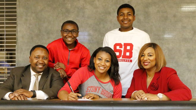 Corning's Taylor Jubilee signs a National Letter of Intent on Tuesday at the Corning-Painted Post High School cafeteria to compete for the Division I Stony Brook track and field team. Alongside her are her parents, Ivan and Krystal Jubilee. In the back are her brothers, Nicholas, left, and Ivan II.