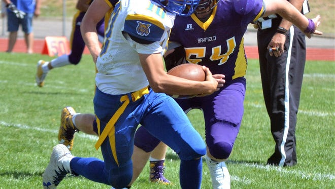 Bloomfield quarterback Rogelio Gonzales, front, scrambles for rare positive yardage away from Bayfield's Kirk Malone (54) during Saturday's 52-0 loss at Wolverine Country Stadium.