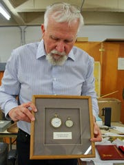Bob Nylen, curator of history at the Nevada State Museum, holds a pair of pocket watches that belonged to the late Nevada state Sen. Bill Raggio and his father, William Raggio Sr. It is part of an exhibit at the state museum on the early life of Raggio.
