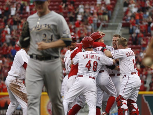 Cincinnati Reds' Todd Frazier, 21, is mobbed by teammates after hitting a game-winning double.