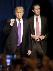Republican presidential candidate Donald Trump, left, arrives with his son Eric during a caucus night rally Tuesday in Las Vegas.