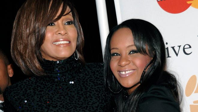 In this Feb. 12, 2011, photo, singer Whitney Houston, left, and daughter Bobbi Kristina Brown arrive at an event in Beverly Hills, Calif.