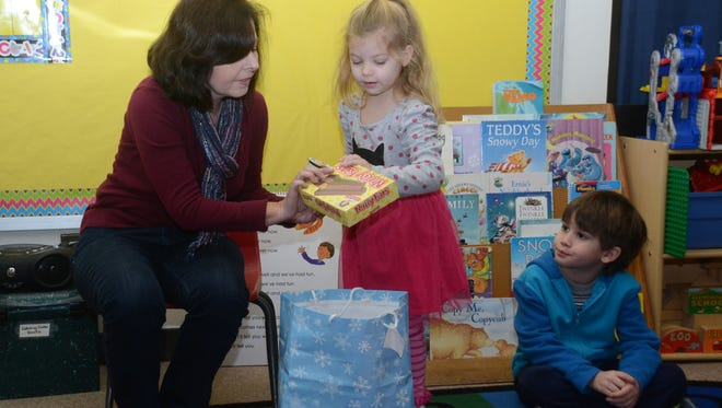 """St. James Episcopal Day School teacher Vicki Durham (far left) helps Jolie Brewer, 4 (center), show the snacks she brought for the class that start with the letter """"N"""" such as Nutty Bars on Wednesday. Jolie and her classmates, including Caleb Fookes (far right), were learning about the letter """"N."""""""