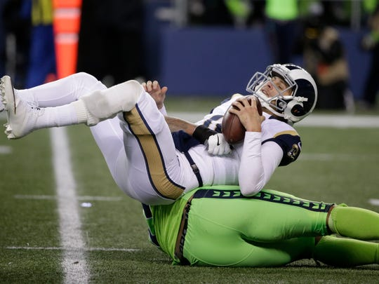 The Seahawks' Michael Bennett brings down Rams quarterback Jared Goff in the second half of Thursday's game in Seattle.