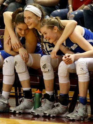 (From left) Adrian Lenawee Christian's Libby Miller, Bree Salenbien and Dani Salenbien hug and celebrate on the bench in the closing seconds of Lenawee Christian's 57-36 win in the Class D state final at Van Noord Arena at Calvin College in Grand Rapids on Saturday, March 17, 2018.