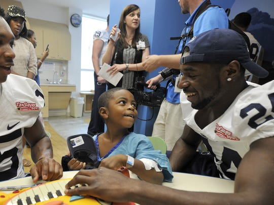 Nick Scott (right) exudes some of the positive energy he's become known for. He and cornerback Grant Haley (15) entertain a new fan  during a team visit to a children's hospital in Jacksonville while preparing for the TaxSlayer Bowl.
