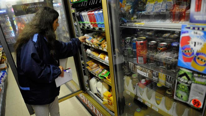 Joyce Coggin searches through the coolers at the J&B Market a convenience store near her house in the Rayon City neighborhood.