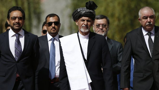 Newly-elected Afghan President Ashraf Ghani Ahmadzai, center, arrives for an inauguration ceremony at the presidential palace in Kabul on Sept. 29.