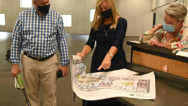 (l-r) Mark Kay, Camille Russo and Kaye Dowell examine architectural renderings of the Junior Achievement Discovery Center.