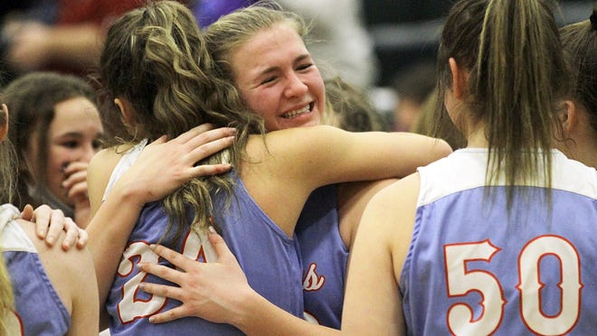 Madison Keil and Bailey Hartsough share a hug following the team's win over NorthWood in the sectional finals on Saturday.