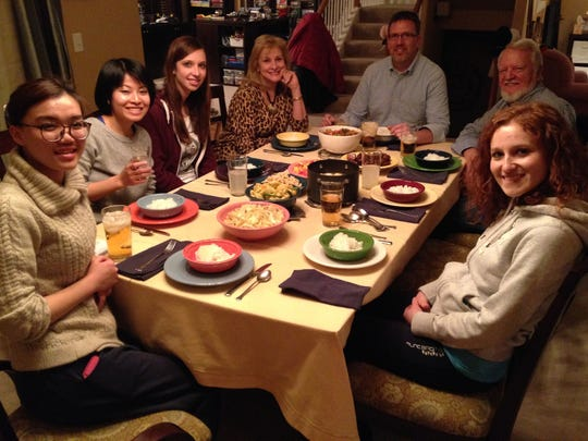 Up with People members from China and Belgium have dinner with a host family.