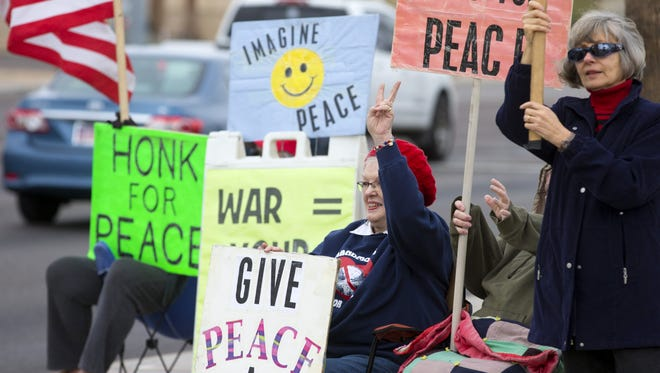 Joan Kroll, 76, of Sun City West (seated, in blue) and Penny Williams, 69, of Sun City West (right), join other members of Grandmothers for Peace at a war protest on Jan. 20, 2018, in Sun City.