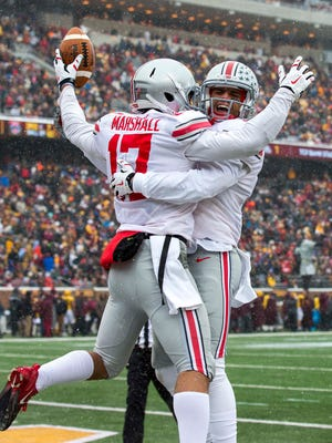 Ohio State running back Jalin Marshall (17) celebrates with wide receiver Devin Smith (9) after scoring a touchdown Saturday in Minneapolis.