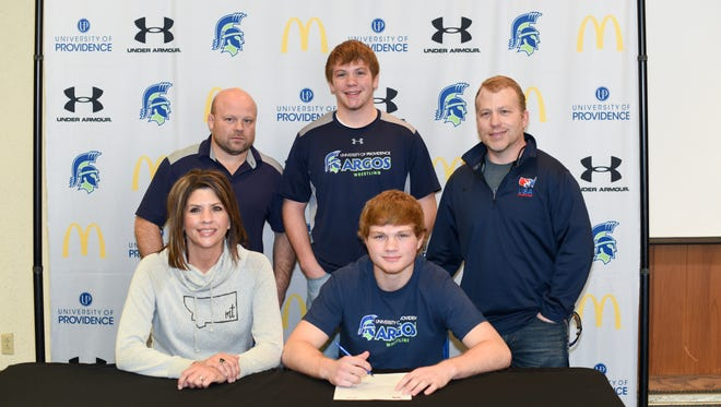 Jordan Komac, pictured with mother Dawnell, UP head coach Caleb Schaeffer (back left), brother Argo team member Jarren, and father Steve, signed with the Providence wrestling team Wednesday.