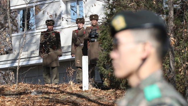 North Korean soldiers look at the South side as a South Korean stands guard near the spot where a North Korean soldier crossed the border on Nov. 13 at the Panmunjom, in the Demilitarized Zone, South Korea, Monday, Nov. 27, 2017.
