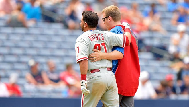 Phillies catcher Wil Nieves is helped off the field after injuring his right quad Wednesday.
