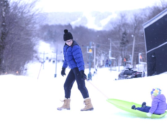 Jonnie Moorhead of South Burlington pulls McKenna, 2, on a sled during a visit to Bolton Valley Resort on the third day of the skiing season there.