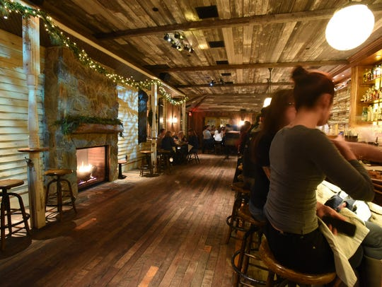 A double-sided fireplace glows between the bar and