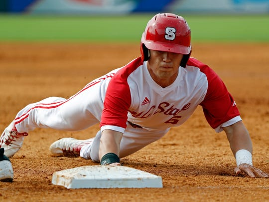 North Carolina State outfielder Brett Kinneman dives back to first base during last year's ACC baseball tournament. The West York grad's power bat is offset nicely by good speed and defensive skills.