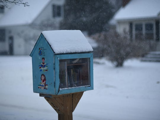 Snow caps the neighborhood little free library on Brewer Parkway early morning on Tuesday, Dec. 12, 2017, as the first significant snowfall of the season hit the region.