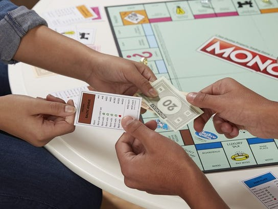 People playing Monopoly game, with one handing over game cash, while the other hands over property card.