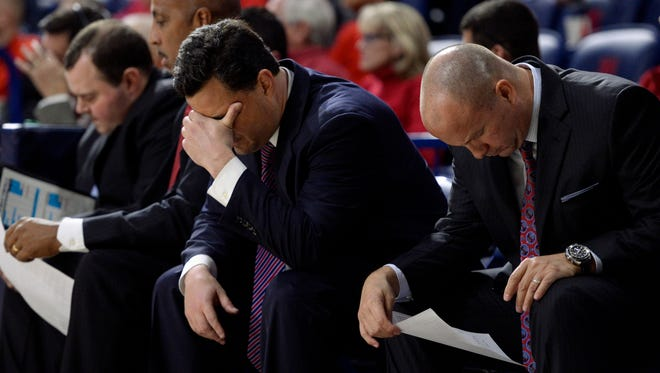 Arizona Wildcats head coach Sean Miller puts his head in his hand while sitting on the bench next to assistant coach Mark Phelps (right) during the second half against the Long Beach State 49ers at McKale Center.