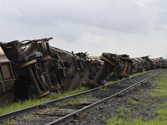 More than 10 empty BNSF Railway cars lie on the ground