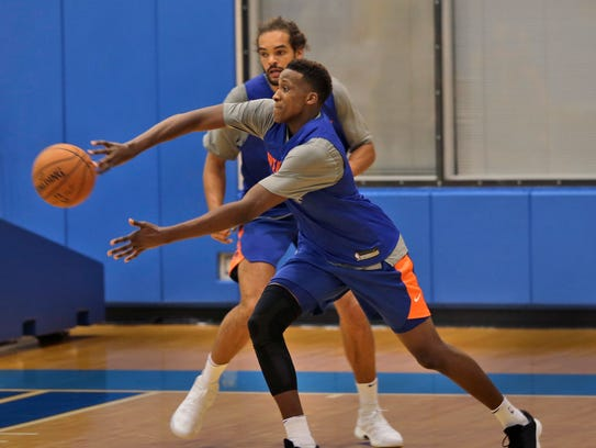 Knicks' Frank Ntilikina, front, passes in front of