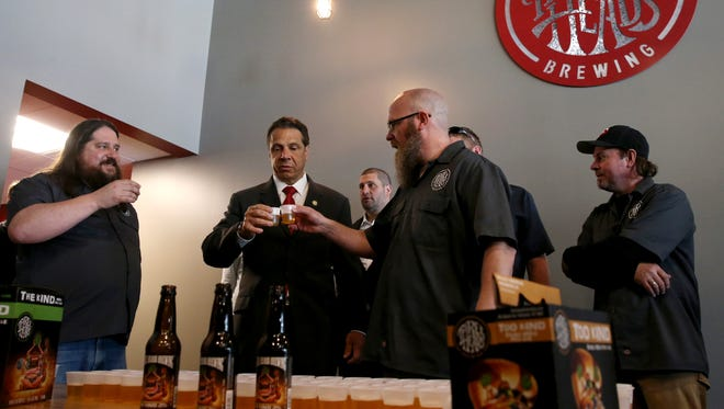 Gov. Andrew Cuomo toasts Geoff Dale, and Brian Johnson of Three Heads Brewery. Cuomo was in Rochester pressing for reform of state liquor laws to help boost  the craft beer, wine and spirits industry.