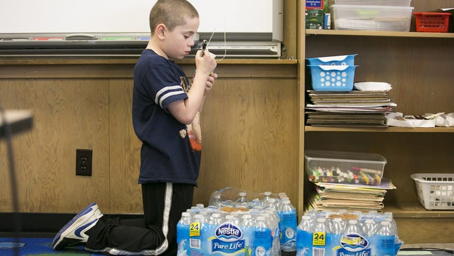 Fourth grader Tyson Turner writes his name on a water bottle at Valley Inquiry Charter School in Salem on March 16, 2016. Students and staff began drinking bottled water in March 2015, after several years of the school struggling to rid the water supply of lead and copper contaminants. Valley Inquiry is among 46 public water systems in Oregon that have exceeded Environmental Protection Agency regulatory limits for lead in drinking water during the past four years.