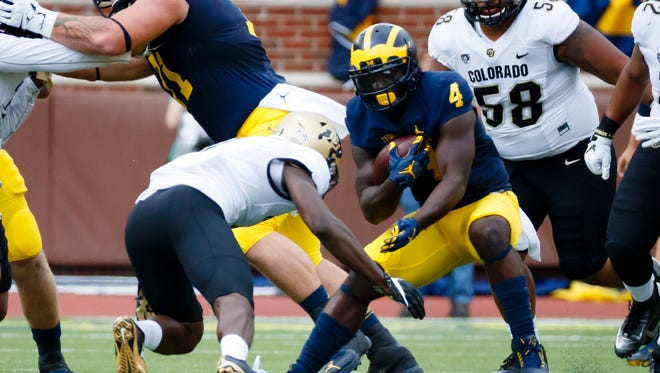 Sep 17, 2016; Ann Arbor, MI, USA; Michigan Wolverines running back De'Veon Smith rushes in the first quarter against the Colorado Buffaloes at Michigan Stadium.