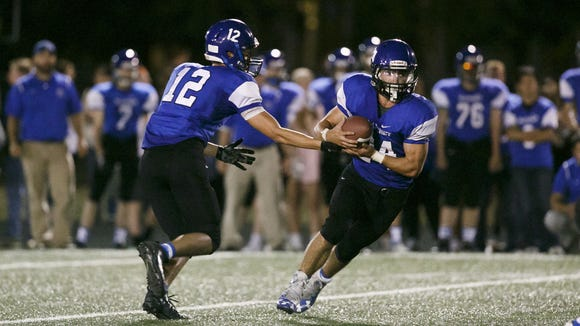 Blanchet's RJ Veliz (12) hands the ball off to Nicholas Orlandini (24) in the fourth quarter of a game against Salem Academy on Friday, Sept. 16, 2016, at Salem Academy. The Salem Academy Crusaders won 14-10 in their first victory over Blanchet since 2011.